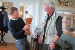 Rolf Wagner übergibt Michael Laub ein großes Glas mit Bier für viele Zwischenschlucke